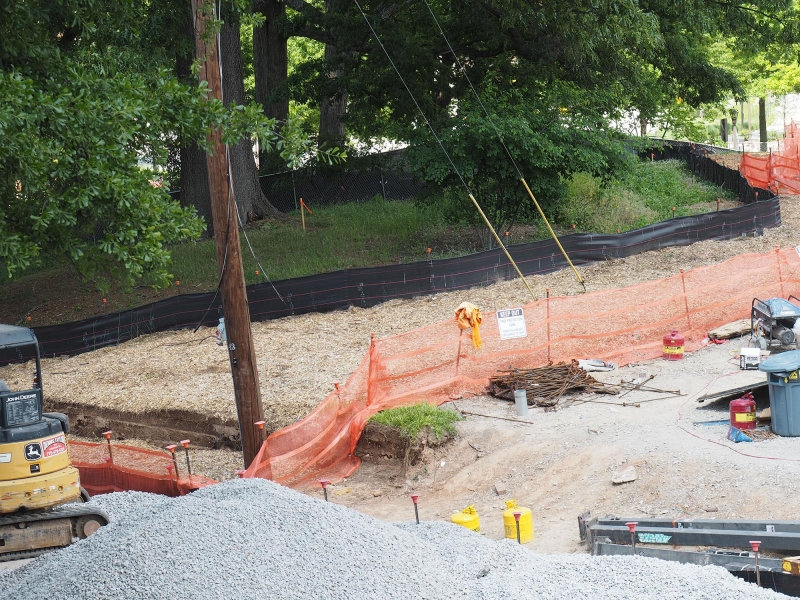 Figure 3. The black silt fence to the back of the picture is supported by metal stakes. In front of the fence is mulch generated from magnolia trees that were removed from the site prior to the beginning of construction.
